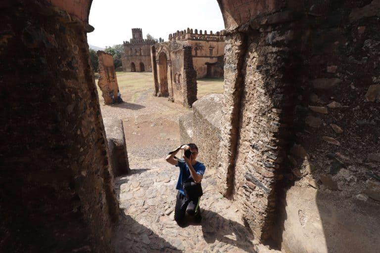 Boy takes photos of the ruined castles in Gondar