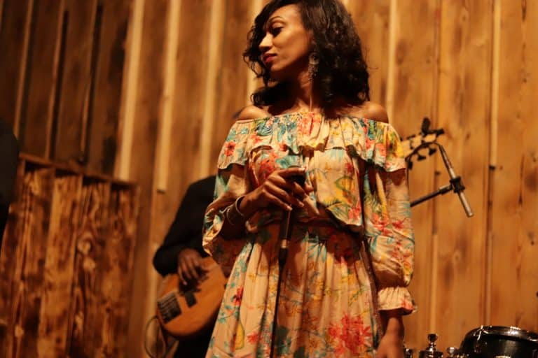 An Ethiopian woman in a floral dress singing on stage