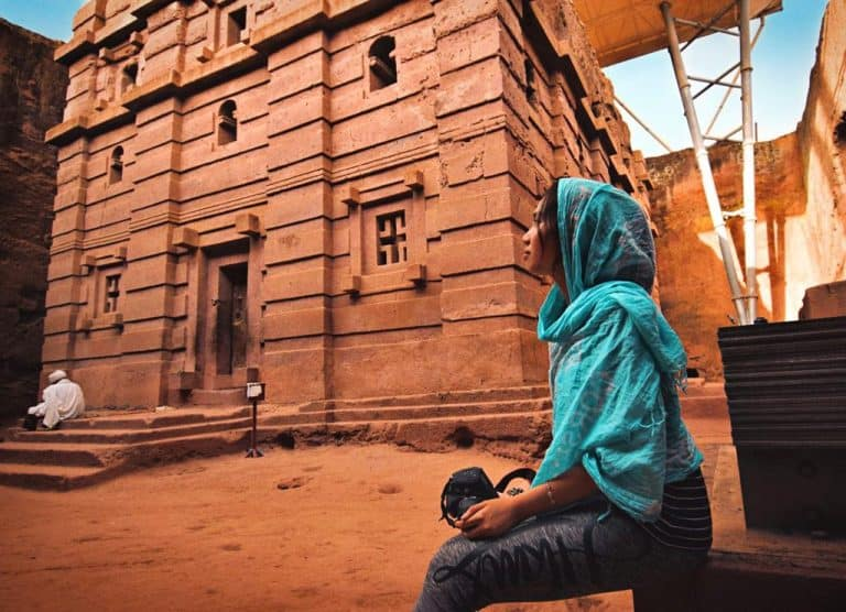 Estella holding her camera, wearing a head scarf, sitting in front of a church in Lalibela