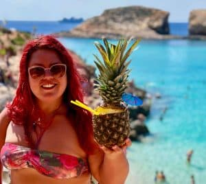 Jasmine holding a pineapple drink standing at a sandy beach with shallow blue water