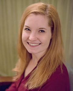 Jenn's author pic showing her smiling into the camera in portrait mode