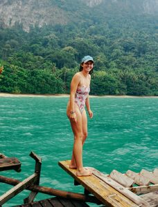 Kat's author bio pic of herself standing on the edge of waters on an island in Vietnam