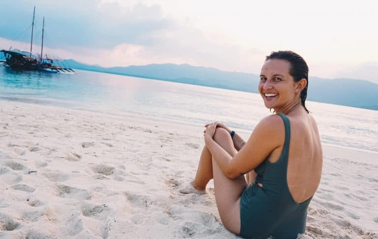Kat sitting on a sandy beach with clear waters looking back into the camera