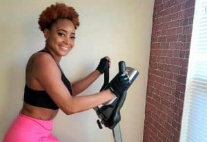 SK on an exercise bike in her black sports bra and pink leggings