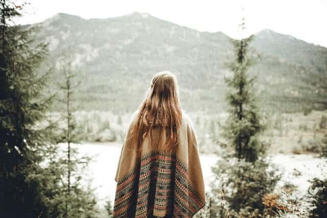 A girl is facing the mountains with a river in front, with her back on the camera
