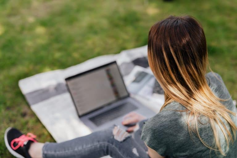 A girl sitting on the grass with her laptop working