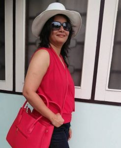Swagata wearing sunglasses and a white hat in her red blouse and red purse smiling at the camera