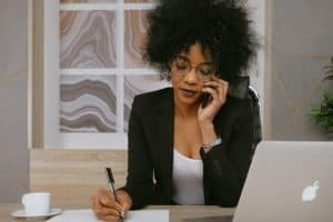 A black woman in suits sitting in front of the table with a MacBook while talking on her phone and writing down notes with a pen and paper