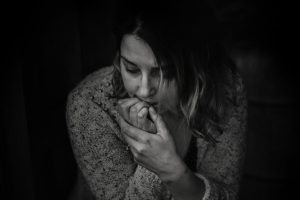 A black and white photo of a woman biting her nail looking sad and worried