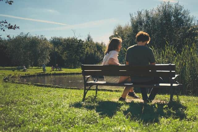 A couple sitting on a bench by the lake in a green park