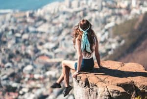 A girl with a bandana sitting on a cliff overlooking a coastal city in a tank top and shorts with sneakers